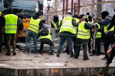 Plusieurs Gilets Jaunes travaillent ensemble pour monter une barricade