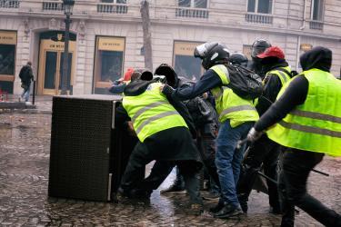 Des Gilets Jaunes se protègent du canon à eau